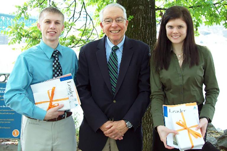 John Prados poses with two students.